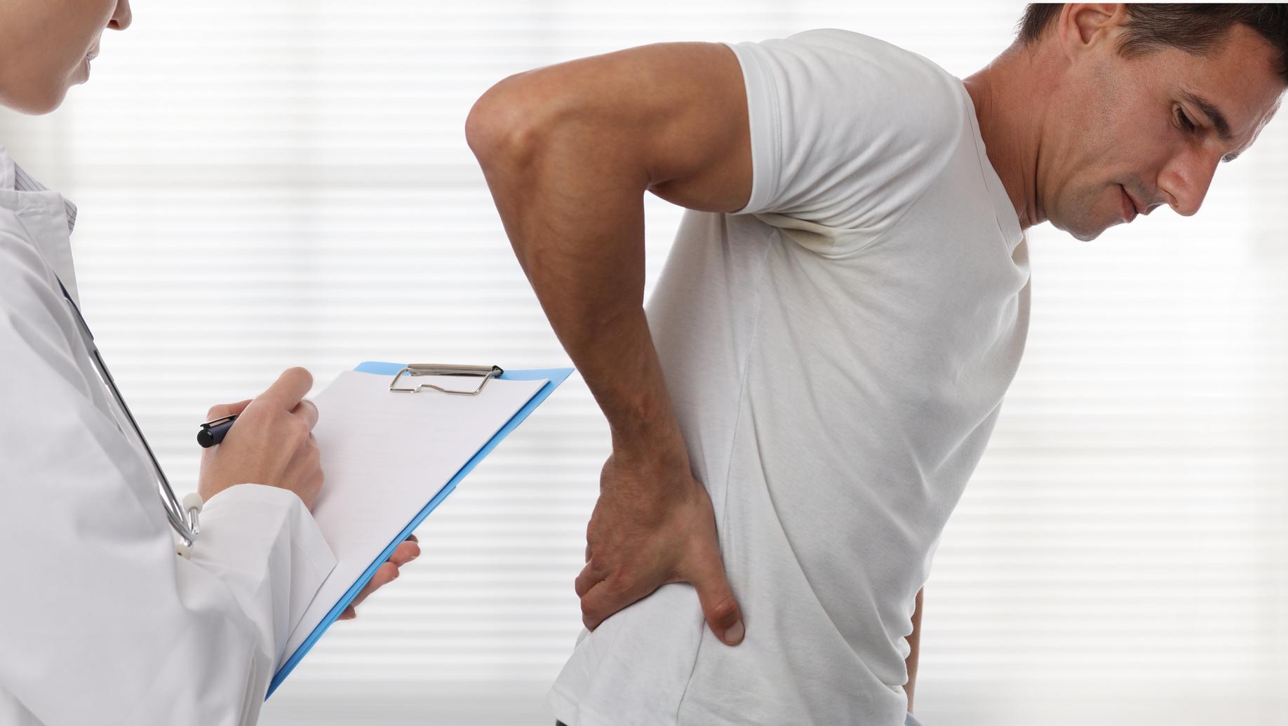 Mann fasst während einer ärztlichen Untersuchung mit einer Hand an seinen schmerzenden Rücken
